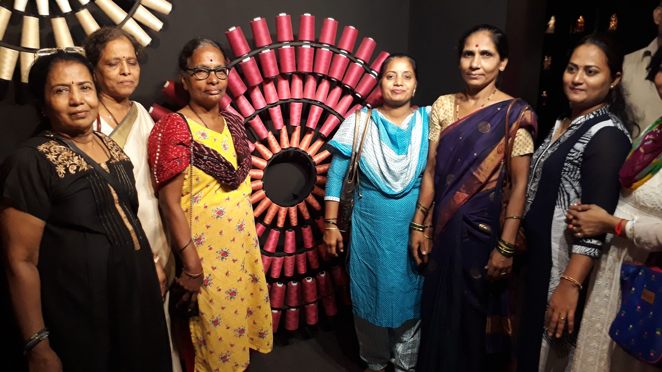 Few beneficiaries standing in front of an innovative model made of different thread roll