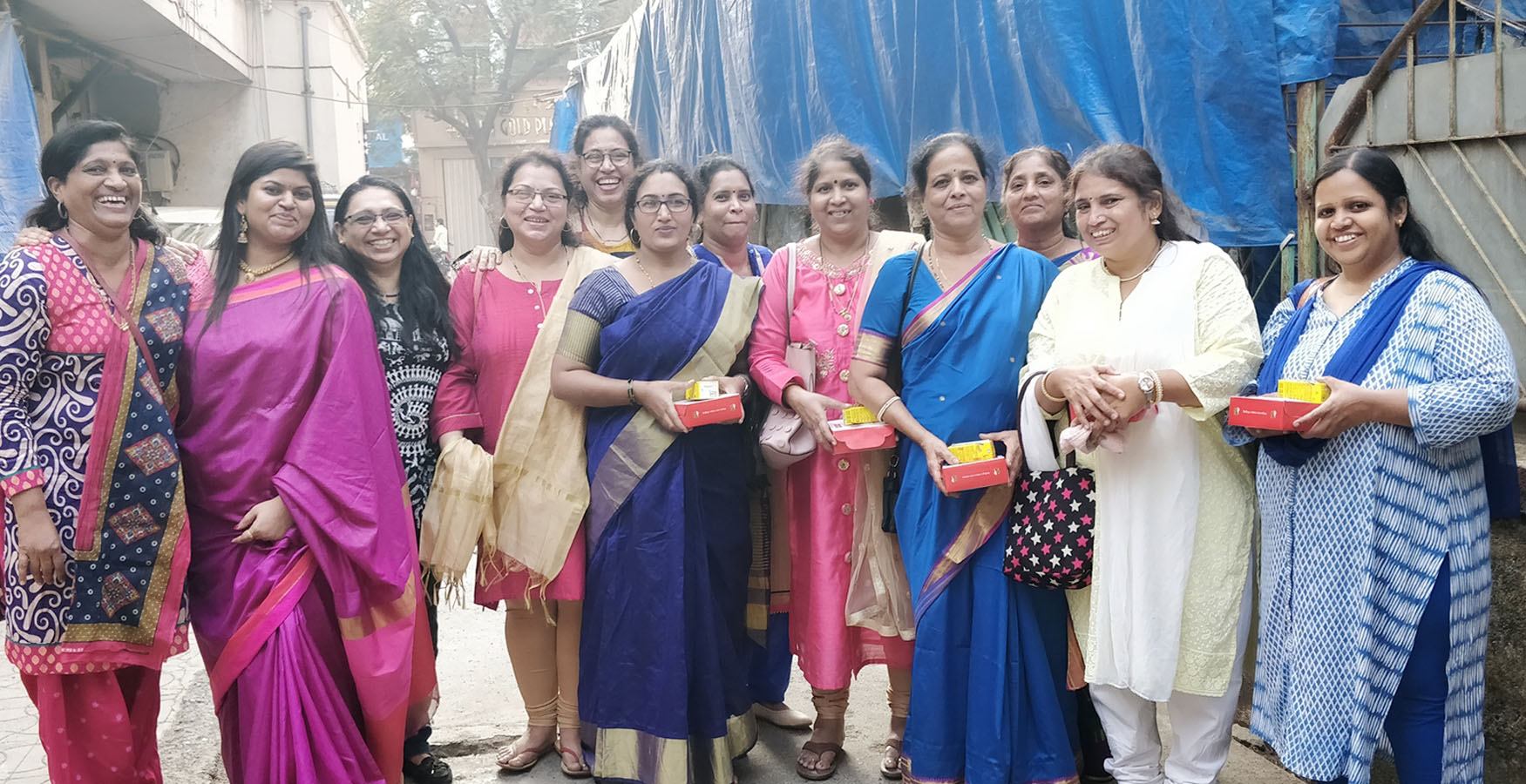 Batch of beneficiaries from Tardeo Hamaara Sapna, staff and teacher smiling into the camera near the centre