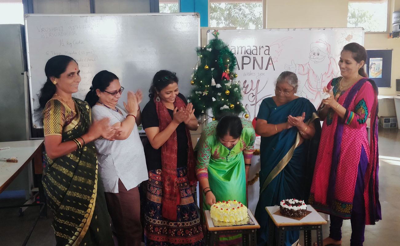 Teachers and staff watch as a student cuts one of the cakes made by Ms. Vrushali. What a sweet Christmas !