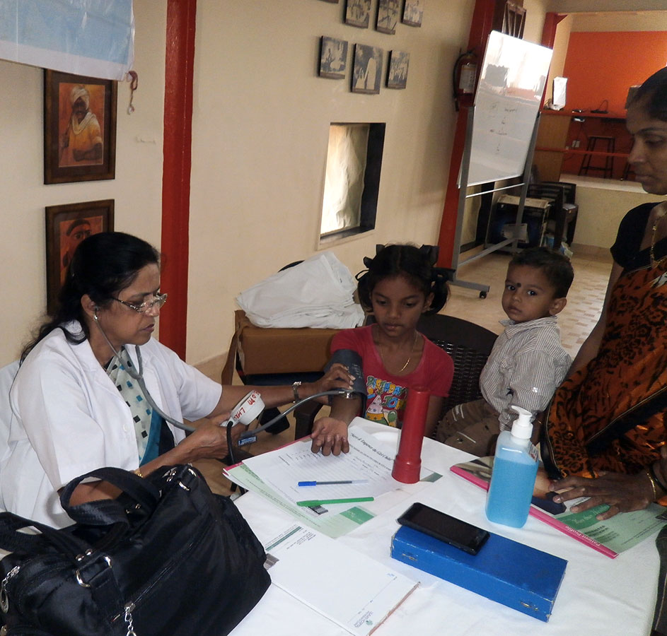 Beneficiary getting her daughter examined at the Medical Camp conducted by Lilavati Hospital (March, 2014)