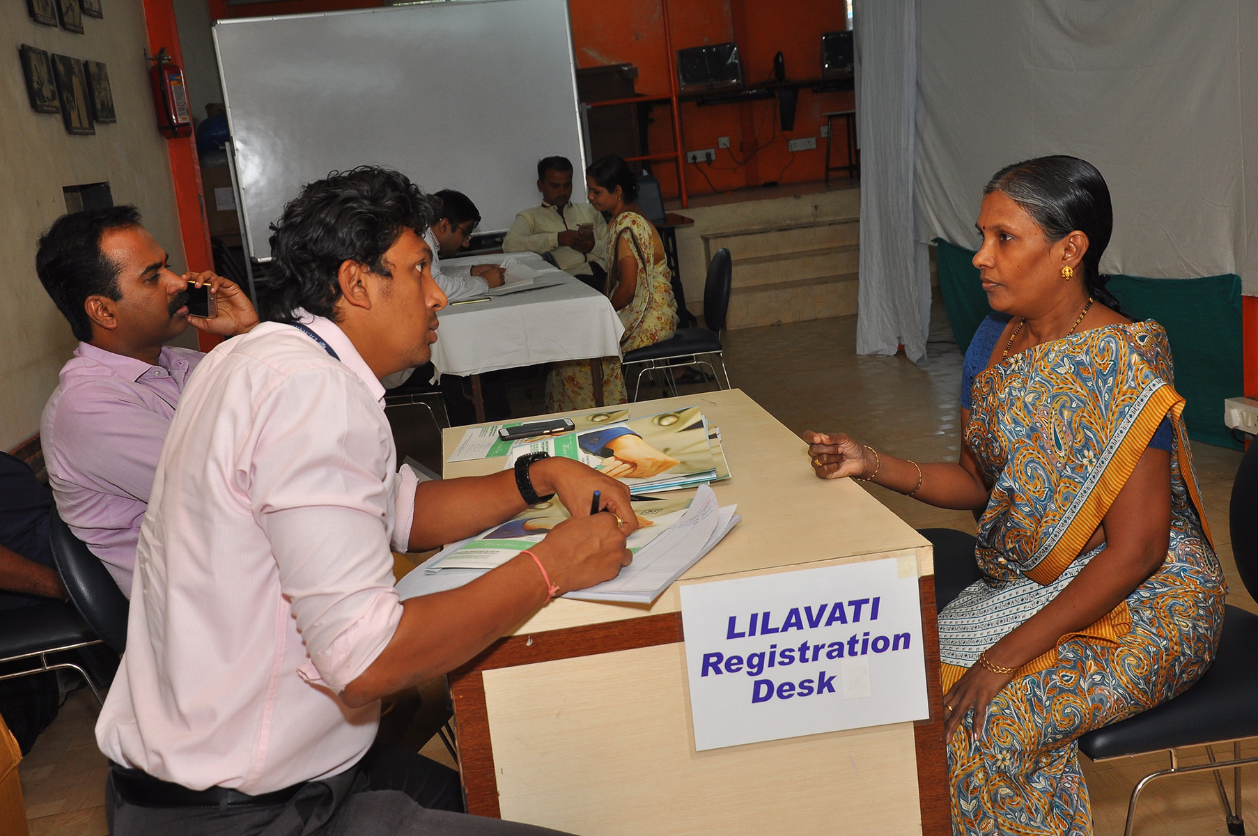 Lilavati Hospital & Research Centre representative noting the registration details of the beneficiaries.